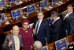 From left, Carlos Lozada, Victoria Sandino, Pablo Catatumbo, Marco Calarca and Olmedo Ruiz, all former members of the demobilized Revolutionary Armed Forces of Colombia, arrive at Congress to take up seats in the newly elected legislature, in Bogota, Colombia, July 20, 2018.
