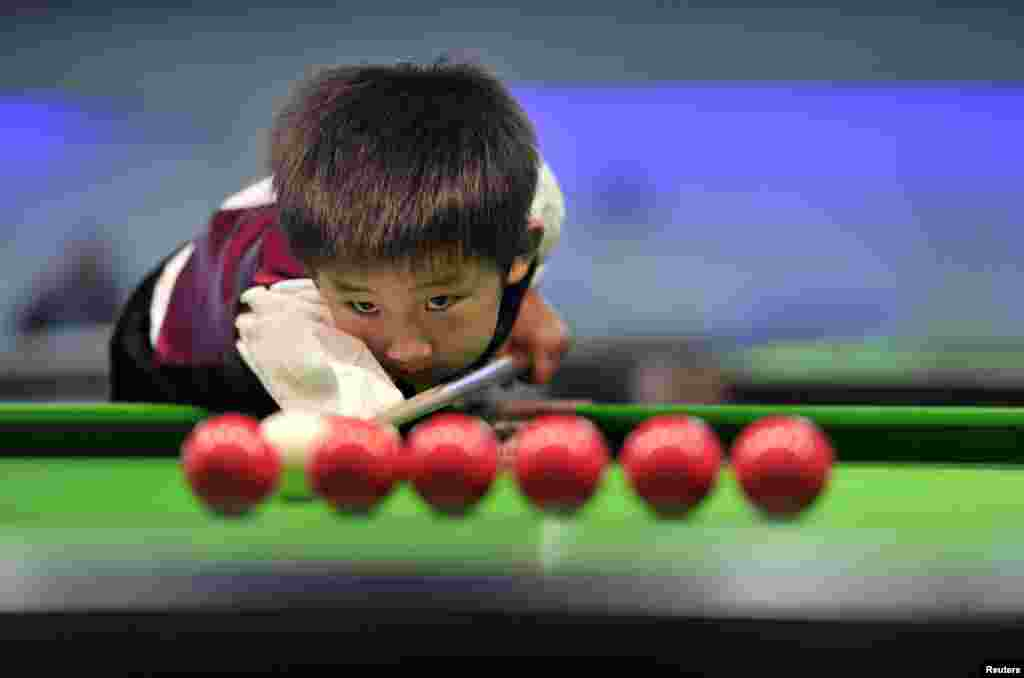 Three-year-old Wang Wuka practises before playing snooker with seven-time World Championship winner Stephen Hendry of Britain in Beijing, Sept. 22, 2013.