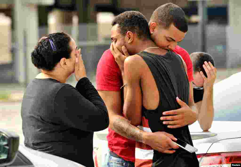 Friends and family members embrace outside the Orlando Police Headquarters during the investigation of a shooting at the Pulse night club, in Orlando, Florida, where as many as 50 people were killed and at least 53 people were injured after a gunman opened fire.