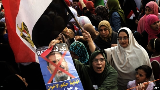 Opposition protesters shout slogans and show a defaced poster of their president as they gather in thousands at the Presidential Palace to protest against Egyptian President Mohamed Morsi and the Muslim Brotherhood in Cairo, July 2, 2013.