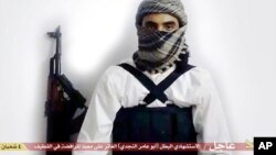 "FILE - This image taken from a militant website associated with Islamic State extremists, posted May 23, 2015, purports to show a suicide bomber with the Arabic text below referring to him as a ""heroic martyr."""