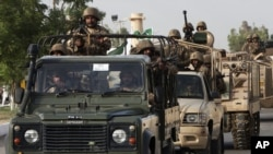 FILE - Pakistani army troops ride military vehicles following an operation launched against a terror group in Karachi, Pakistan, June 16, 2014.