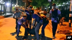 People help an unidentified injured person after a group of gunmen attacked a restaurant popular with foreigners in the Bangladeshi capital Dhaka.