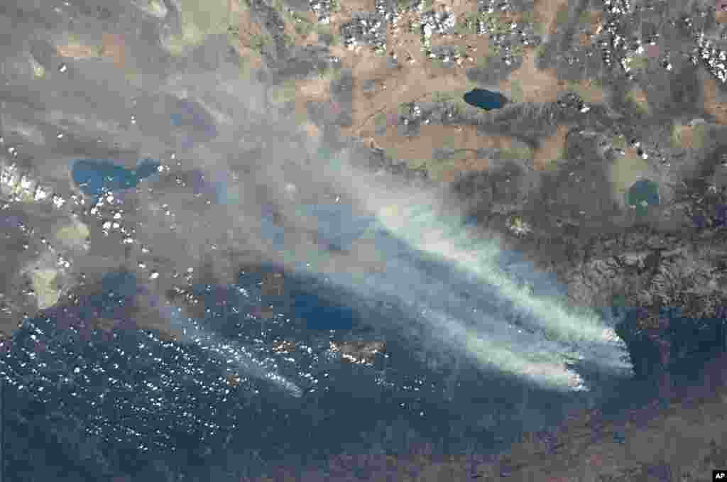 This photo released by NASA astronaut Karen Nyberg shows a view of the California wildfires from the International Space Station, August 26, 2013.