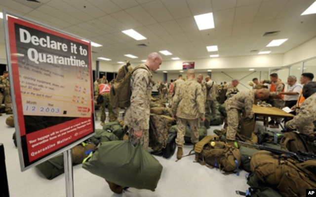 FILE - United States Marines complete quarantine checks as they arrive at a Royal Australian Air Force Base in Darwin.