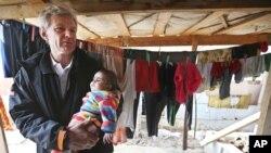 Penasihat khusus PBB tentang Suriah, Jan Egeland menggendong seorang bayi di kamp pengungsi Suriah di Marej, Lembah Bekaa, Lebanon (foto: dok).