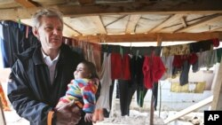 FILE - U.N. special adviser Jan Egeland holds a Syrian baby during his visit to a refugee camp in the town of Marej in the Bekaa valley, east Lebanon, Feb. 25, 2015.