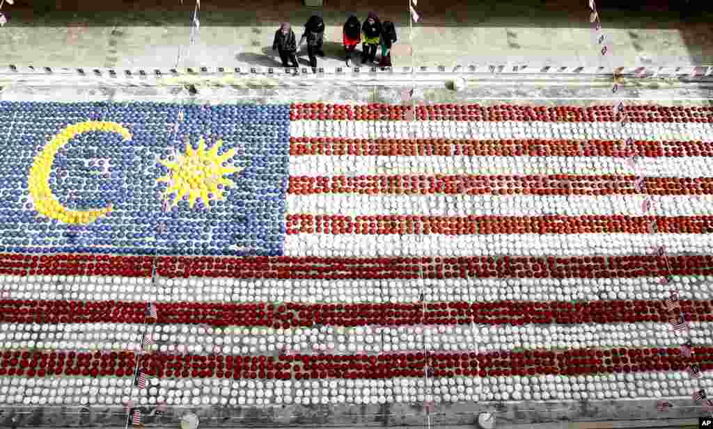 말레이시아 수도 쿠알라룸푸르 학생들이 코코넛 껍질을 모아만든 거대한 국기를 바라보고 있다.