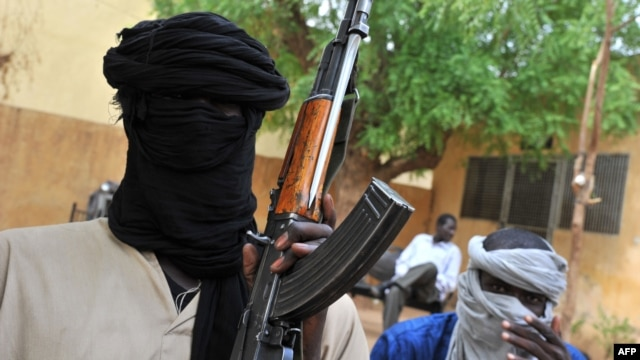 A picture taken on July 16, 2012 shows fighters of the Islamist group Movement for Unity and Jihad in West Africa (MUJAO) sitting in the courtyard of the Islamist police station in Gao.