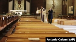 FILE - In this March 28, 2020, file photo, Don Marcello Crotti, left, blesses the coffins with Don Mario Carminati in the San Giuseppe church in Seriate, Italy. (AP Photo/Antonio Calanni, File)