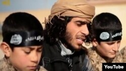 А YouTube screen grab from an Islamic State propaganda video shows an IS recruiter with two child soldiers. Children as young as eight years old are reportedly being trained to serve in roles ranging from spies, to front line soldiers, to suicide bombers.