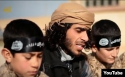 "FILE - А screen grab from an Islamic State propaganda video shows an Islamic State recruiter with two child soldiers at an unknown location. Experts warn that not enough thought is being given about what to do with so-called ""cubs of the caliphate"" — both the offspring of foreign recruits as well as Syrian and Iraqi children enlisted into terror ranks."