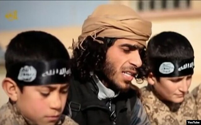 FILE - А screen grab from an Islamic State propaganda video shows an Islamic State recruiter with two child soldiers at an unknown location. Experts warn that not enough thought is being given about what to do with so-called
