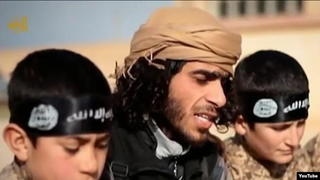 """ARCHIVO - Una captura de pantalla de un video de propaganda del Estado Islámico muestra a un reclutador del Estado Islámico con dos niños soldados en un lugar desconocido. Los expertos advierten que no se está dando suficiente atención sobre qué hacer con los llamados """"cachorros del califato"""": tanto los descendientes de reclutas extranjeros como los niños sirios e iraquíes se alistaron en filas terroristas."""