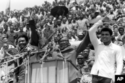 "FILE - Zaire's President Mobutu Sese Seko, center, raises the arms of heavyweight champion George Foreman, left, and Muhammad Ali, right, in Kinshasa, Zaire, Sept. 22, 1974. The two boxing greats faced off in the legendary ""Rumble in the Jungle"" fight in Kinshasa, Oct. 29, 1974."