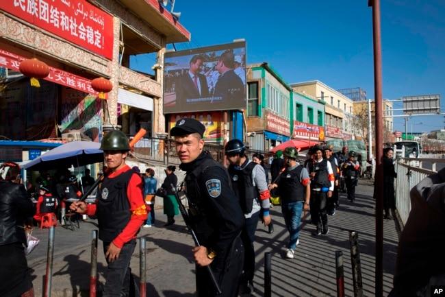 一名中國警察帶領一隊武裝民兵在新疆和田的市場外巡邏。 (2017年11月3日)