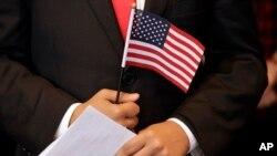 手握美國國旗等待宣誓入美國國籍的人