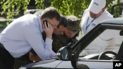 Alexander Hug, deputy head of the OSCE mission to Ukraine, left, his colleagues and a pro-Russian rebel, 2nd right, examine a map as they try to estimate security conditions around the site of the crashed Malaysia Airlines Flight 17 in the city of Donetsk