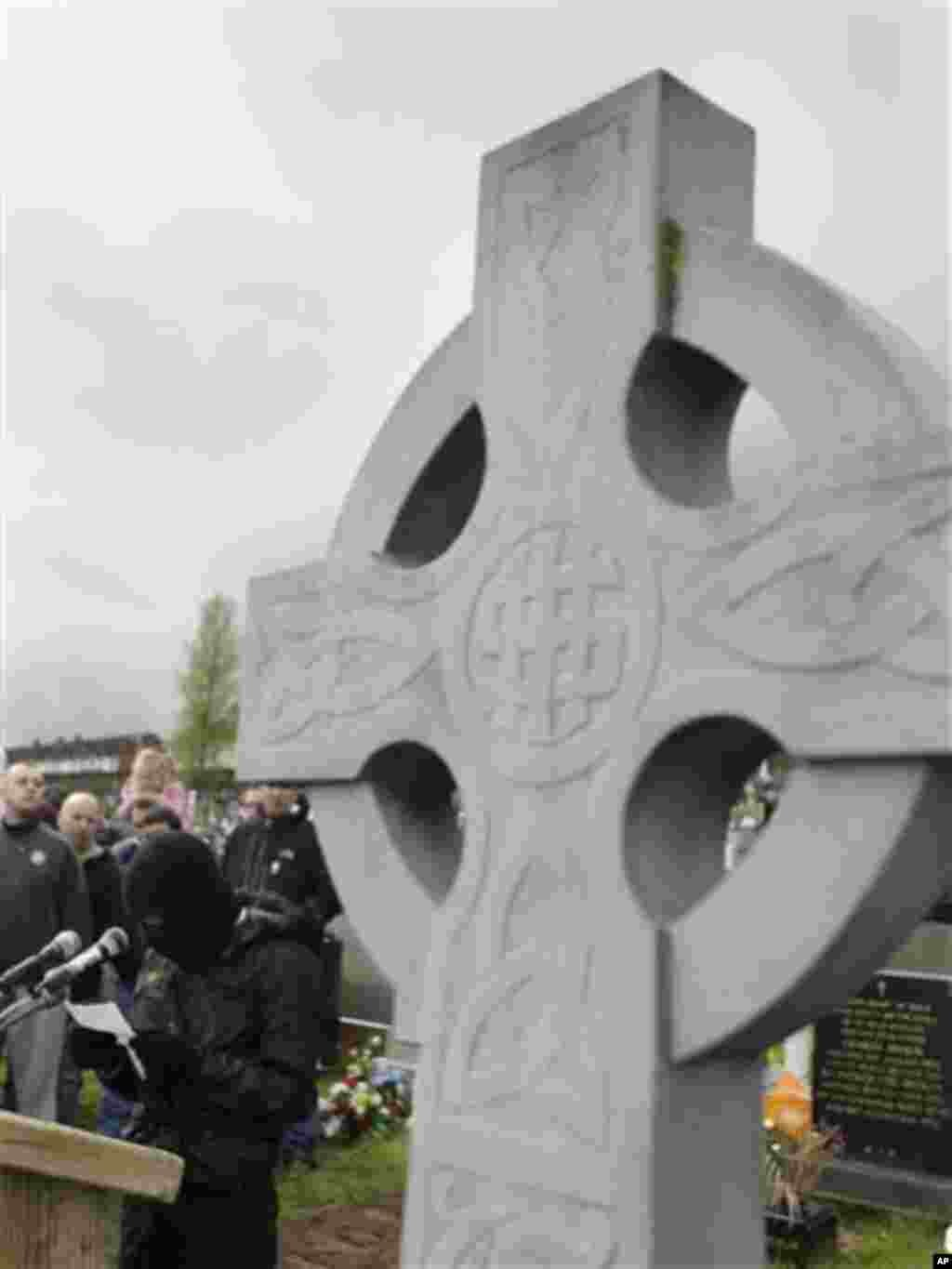 A masked member from the dissident terror group the Real Irish Republican Army (RIRA) reads a statement to supporters at Creggan Cemetery, Londonderry, Northern Ireland, Monday, April 9, 2012. Hundreds of dissident sympathizers gathered Monday for a comm
