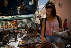 Tourist Sophia Compton from Chicago looks for souvenirs at a market in Santa Clara, Cuba, Sept. 1, 2016.