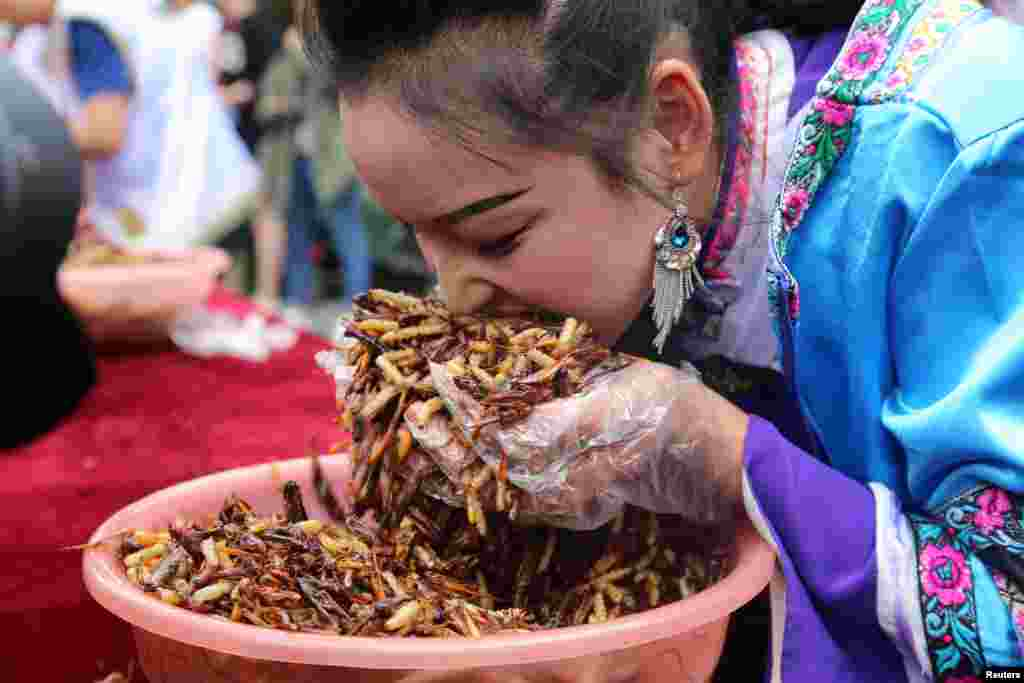 A woman participates in an insect-eating competition in Lijiang, Yunnan province, China, June 25, 2017.