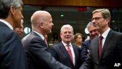 Britanski šef diplomatije Vilijam Hejg (L) rukuje se sa nemačkim kolegom Gvidom Vesterveleom uoči današnjeg sastanka ministara EU u Briselu