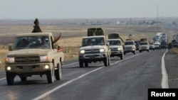 FILE - Convoy of peshmerga vehicles makes its way to the Turkish-Syrian border, near the town of Kiziltepe, in the southeastern Mardin province, Turkey, Oct. 29, 2014.