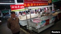 Seorang pria berjalan melintasi sebuah kios penjualan daging yang tutup di distrik Minhang district, selatan Shanghai (Foto: dok). Kios ini milik pria 27 tahun yang meninggal akibat virus flu burung H7N9 bulan lalu.China melaporkan adanya kasus baru tersebarnya virus ini di propinsi Henan, Minggu (14/4).