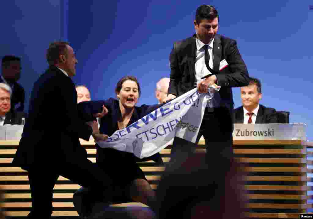 An environmental activist is pulled from the stage during the annual shareholders meeting of German power supplier RWE in Essen.