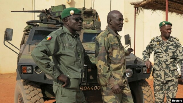 Malian military soldiers stand near an armored vehicle that belongs to the French Army at the Malian military Command Post in Sevare, northeast of the capital Bamako, January 25, 2013.