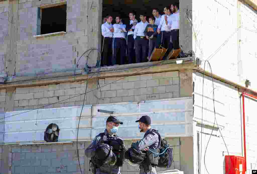 Ultra-Orthodox Jewish seminary students look at Israeli police as they arrive to shutter the Jewish seminary that had opened in violation of coronavirus lockdown rules in Ashdod, Israel.