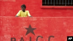 Boy stands by sign of Guinea-Bissau's ruling political party on election day in the capital, Bissau, March 18, 2012.