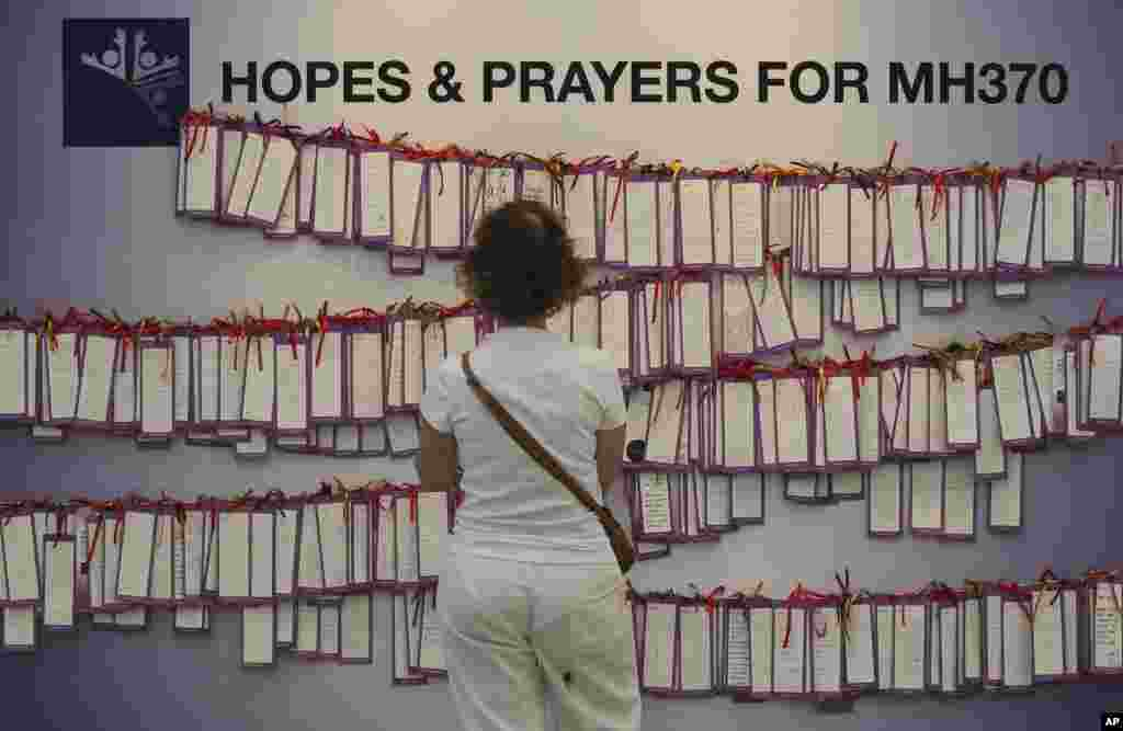 A woman read message cards for passengers aboard flight MH370 at a shopping mall in Kuala Lumpur, March 24, 2014.