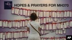 一位女士阅读马来西亚吉隆坡某购物中心张挂的为失踪马航班机乘客所写的祝福卡。(2014年3月24日)