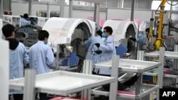 上海生產醫療設備的西門子工廠工人戴著口罩在生產線上工作。 (2020年2月24日)