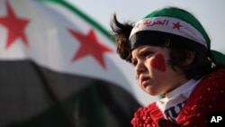 A girl wears a headband in the colors of the Syrian revolutionary flag and painted her face with hearts during a protest in front of the Syrian embassy in Amman, Jordan, May 17, 2013.