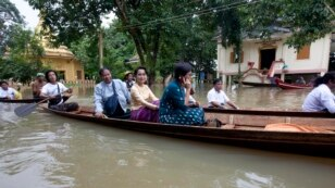 Myanmar opposition leader Aung San Suu Kyi, center, rides a boat on her way to a monastery where flood victims are sheltered, in Bago, 80 kilometers northeast of Yangon, Myanmar.