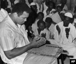 FILE - Muhammad Ali prays with a class of Muslim boys at Dafaalah el Sa'em Mosque in Khartoum, Sudan, Nov. 23, 1988.