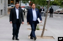 Fired Catalan vice president Oriol Junqueras, right, arrives at the national court in Madrid, Nov. 2, 2017. Some of the 14-member ousted Catalan Cabinet were expected to appear before a judge in Madrid for questioning as part of a rebellion inquiry.