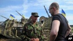 Thủ tướng Ukraine Arseniy Yatsenyuk nói chuyện với sĩ quan trong chuyến thăm đơn vị quân đội gần thị trấn miền đông Slovyansk, ngày 16/7/2014.