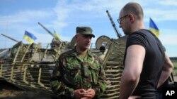 7月16日,乌克兰总理亚采尼克(右)在斯洛文斯克外面的陆军阵地视察时与一名军官谈话。