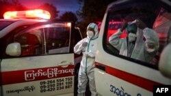 ရန္ကုန္ၿမိဳ႕ရွိ ရပ္ကြက္တခုက ကိုဗစ္သံသယလူနာမ်ားကို Quarantine စင္တာဆီ ေခၚဖို႔ ျပင္ဆင္ေနၾကတဲ့ PPE ဝတ္စံုဝတ္ထားတဲ့ ပရဟိတလုပ္သားမ်ား။ (ေအာက္တိုဘာ ၁၇၊ ၂၀၂၀)