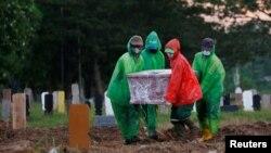 Para petugas pemakaman mengusung peti jenazah korban virus corona (COVID-19) untuk dimakamkan, Jakarta, 31 Maret 2020. (Foto: Reuters)