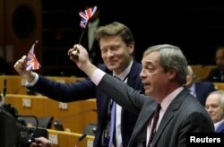 Brexit Party leader Nigel Farage along with other MEPs wave British flags ahead of a vote on the Withdrawal Agreement at the European Parliament in Brussels, Jan. 29, 2020.