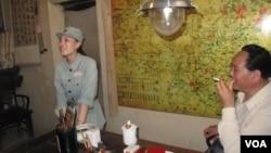 在中共革命胜地西柏坡,一名扮演毛泽东的特型演员等待与游客合影,一名穿着八路军服的女子在一旁收费。(2013年)