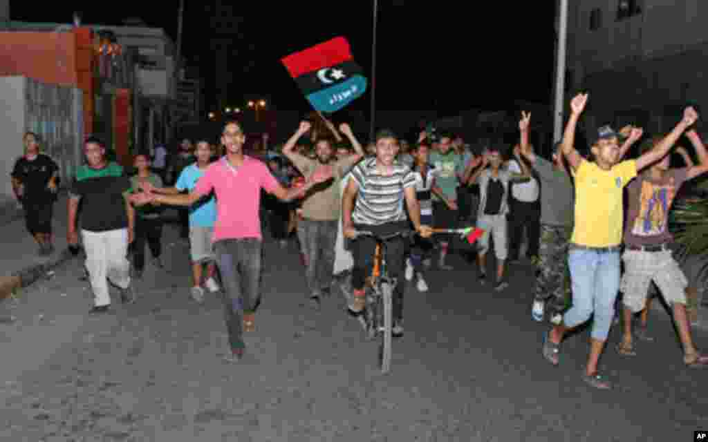 People in Tajura, a suburb of Tripoli, celebrating in the early morning on August 22, 2011 after Libyan rebels surged into Tripoli in a final drive to oust leader Moamer Kadhafi, seizing swathes of the capital including the symbolic Green Square and arres