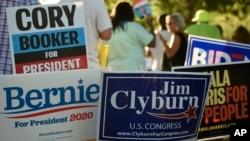 各路民主黨總統參選人的支持者在眾議院多數黨黨鞭吉姆·克萊伯恩主辦的一次活動的場外為豎立競選標牌。 (2019年6月21日)