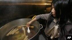 Châu Đặng Haller, chủ nhà hàng Việt Brodard Chateau, thử nước dùng phở trong bếp của nhà hàng tại Garden Grove, California.