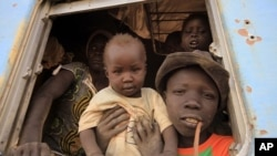 A South Sudanese family waits inside a train in Khartoum to be transported to Wau in South Sudan, March 1, 2012.