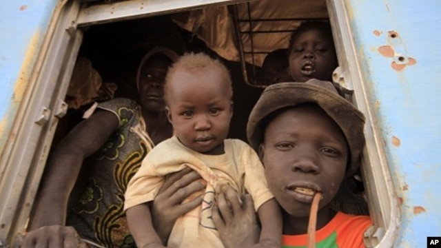 A South Sudanese family waits inside a train in Khartoum to be transported to Wau in South Sudan, March 1, 2012. Last week, 1,700 South Sudanese who lived at Kosti transit camp, south of Khartoum, returned home from the north.
